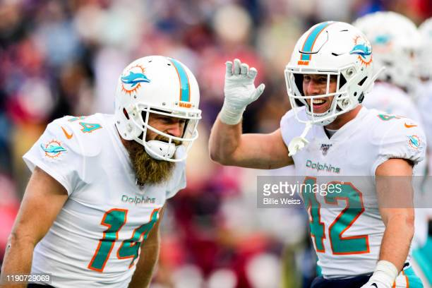 Ryan Fitzpatrick of the Miami Dolphins reacts with Patrick Laird after carrying the ball for a touchdown during the third quarter of a game against...
