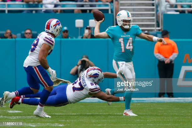 Ryan Fitzpatrick of the Miami Dolphins throws the ball while being pressured by Lorenzo Alexander of the Buffalo Bills during an NFL game on November...