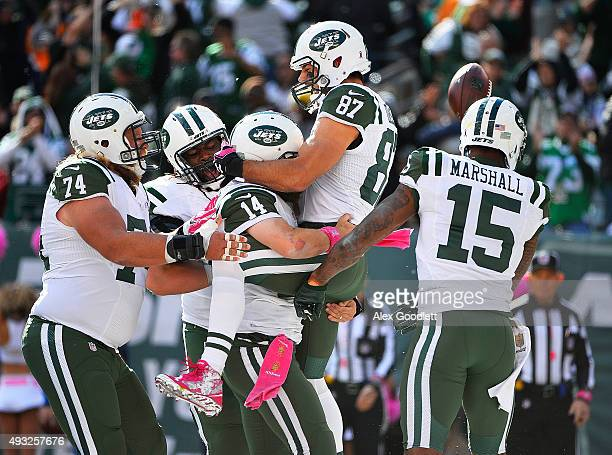 Ryan Fitzpatrick of the New York Jets picks up Eric Decker as he is congratulated by his teammates after scoring a third quarter touchdown against...