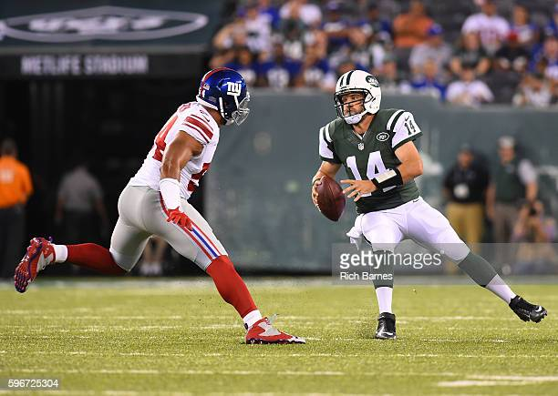 Ryan Fitzpatrick of the New York Jets scrambles out of the pocket as Olivier Vernon of the New York Giants defends during the first quarter at...