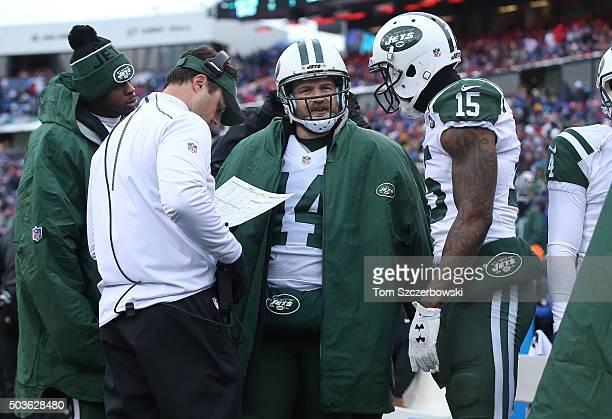Ryan Fitzpatrick of the New York Jets talks to quarterbacks coach Kevin Patullo and Brandon Marshall as Geno Smith listens against the Buffalo Bills...