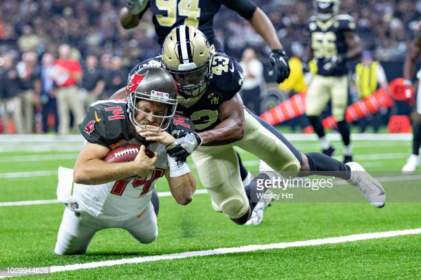 Ryan Fitzpatrick of the Tampa Bay Buccaneers runs the ball for a touchdown and is tackled by Marcus Williams of the New Orleans Saints at...