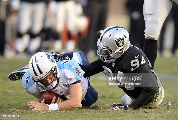 Ryan Fitzpatrick of the Tennessee Titans scrambles with the ball and gets tackled by Kevin Burnett of the Oakland Raiders during the fourth quarter...