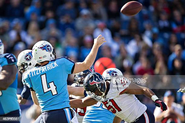 Ryan Fitzpatrick of the Tennessee Titans throws a pass under pressure from Darryl Sharpton of the Houston Texans at LP Field on December 29 2013 in...