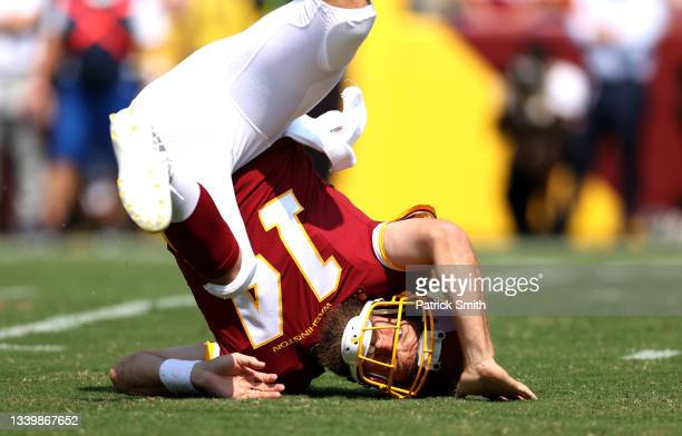 Ryan Fitzpatrick of the Washington Football Team is hit after throwing a pass against the Los Angeles Chargers during the first quarter at FedExField...