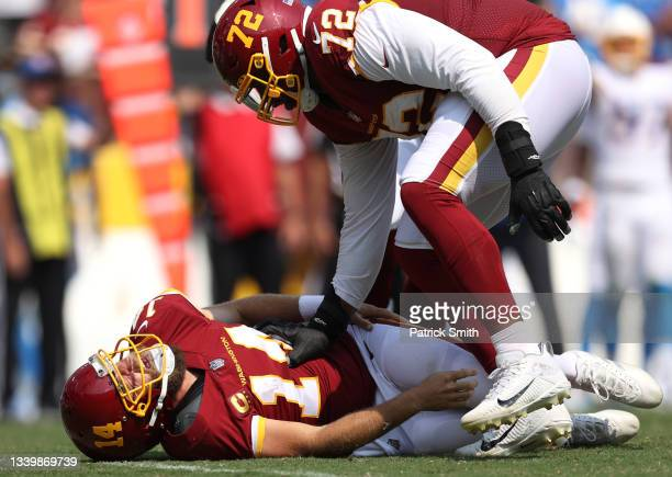 Ryan Fitzpatrick of the Washington Football Team reacts with Charles Leno Jr. #72 after being tackled against the Los Angeles Chargers during the...