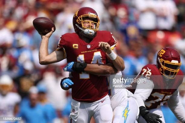 Ryan Fitzpatrick of the Washington Football Team takes a hit against the Los Angeles Chargers during the second quarter at FedExField on September...
