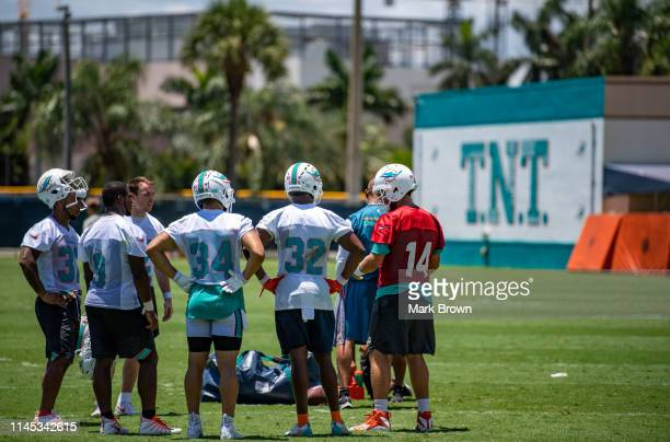 Ryan Fitzpatrick works after practice with running backs Myles Gaskin, Mark Walton, Patrick Laird, Kenneth Farrow, and Kenyon Drake of the Miami...