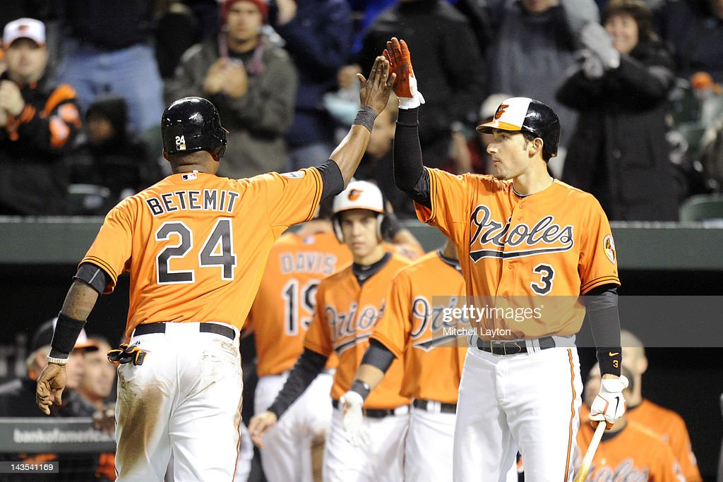 Ryan Flaherty #3 of the Baltimore Orioles congratulates Wilson Betemit #24 for scoring during the second inning of a baseball game against the Oakland Athletics at Oriole Park at Camden Yards on April 28, 2012 in Baltimore, Maryland.