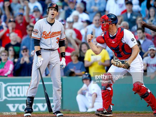 Ryan Flaherty of the Baltimore Orioles reacts after striking out as Ryan Lavarnway of the Boston Red Sox gestures to end the 9th inning to give the...