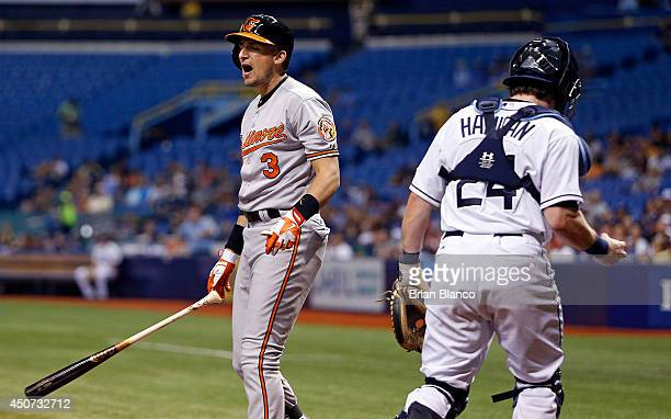 Ryan Flaherty of the Baltimore Orioles reacts as he strikes out swinging in front of catcher Ryan Hanigan of the Tampa Bay Rays with two men on base...