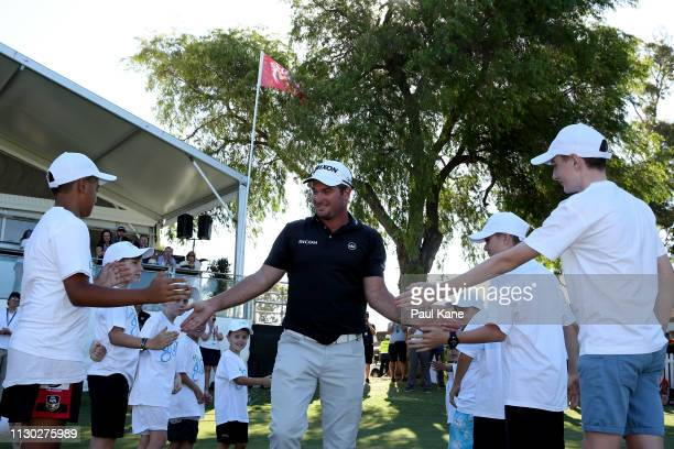 Ryan Fox of New Zealand high fives junior golfers while walking onto the green for presentations after defeating Adrian Otaegui Spain in the final...