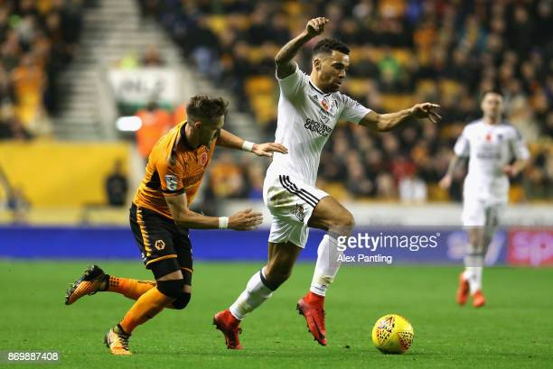 Ryan Fredericks of Fulham is pulled back by Barry Douglas of Wolverhampton Wanderers during the Sky Bet Championship match between Wolverhampton...