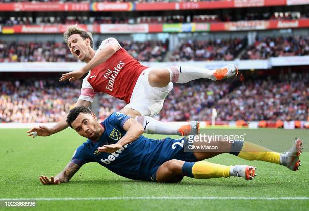 Ryan Fredericks of West Ham United and Nacho Monreal of Arsenal clash during the Premier League match between Arsenal FC and West Ham United at...