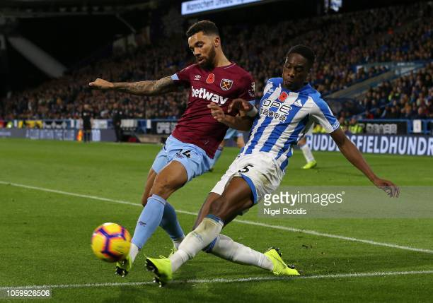 Ryan Fredericks of West Ham United is tackled by Terence Kongolo of Huddersfield Town during the Premier League match between Huddersfield Town and...