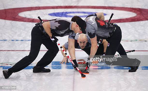 Ryan Fry of Canada plays a stone as Ryan Harnden and EJ Harnden assist during the Men's Gold Medal match between Canada and Great Britain on day 14...