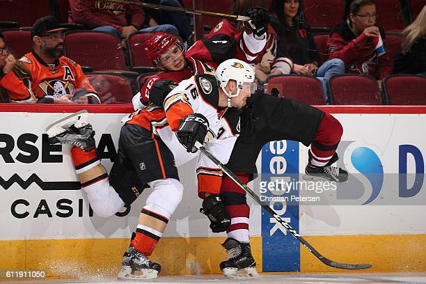 Ryan Garbutt of the Anaheim Ducks lays a body check onto Nick Merkley of the Arizona Coyotes during the second period of the preseason NHL game at...