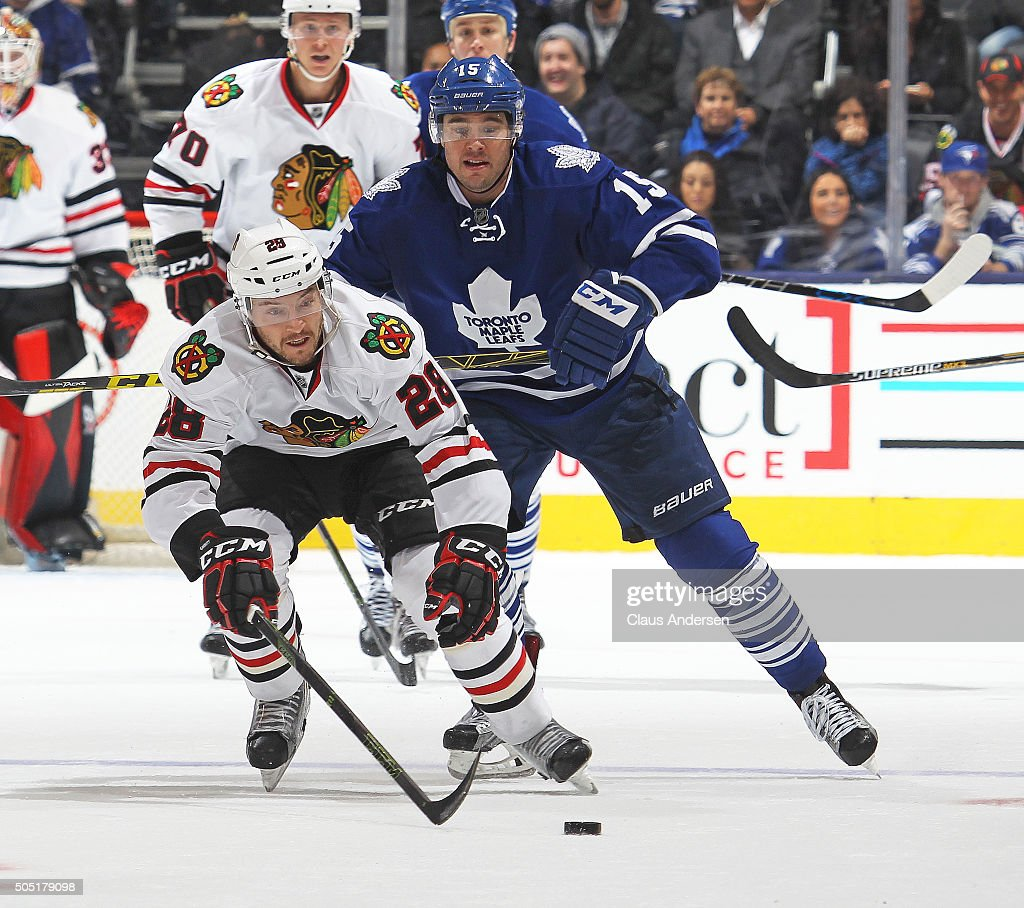 Ryan Garbutt #28 of the Chicago Black Hawks skates after a puck in front of PA Parenteau #15 of the Toronto Maple Leafs during an NHL game at the Air Canada Centre on January 15, 2016 in Toronto, Ontario, Canada. The Black Hawks defeated the Maple Leafs 4-1.