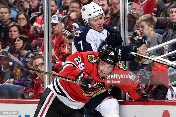 Ryan Garbutt of the Chicago Blackhawks checks Ben Chiarot of the Winnipeg Jets into the boards in the first period of the NHL game at the United...