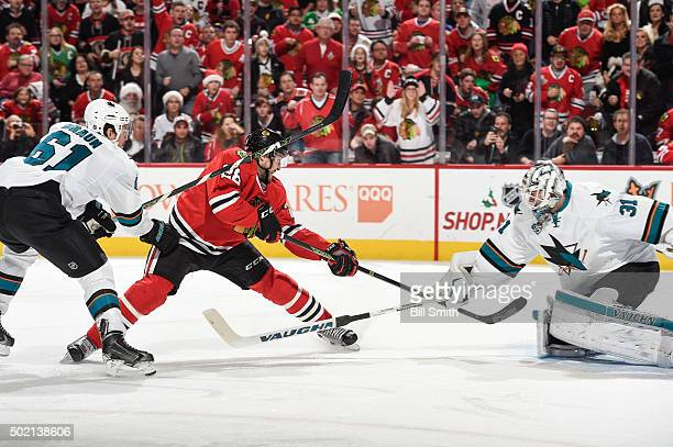 Ryan Garbutt of the Chicago Blackhawks shoots the puck toward goalie Martin Jones of the San Jose Sharks as Justin Braun follows in the third period...