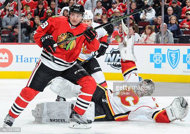 Ryan Garbutt of the Chicago Blackhawks watches the puck fly through the air as goalie Karri Ramo of the Calgary Flames lays on the ice in the third...