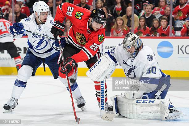 Ryan Garbutt of the Chicago Blackhawks works to get at the puck against goalie Kristers Gudlevskis of the Tampa Bay Lightning as Cedric Paquette...