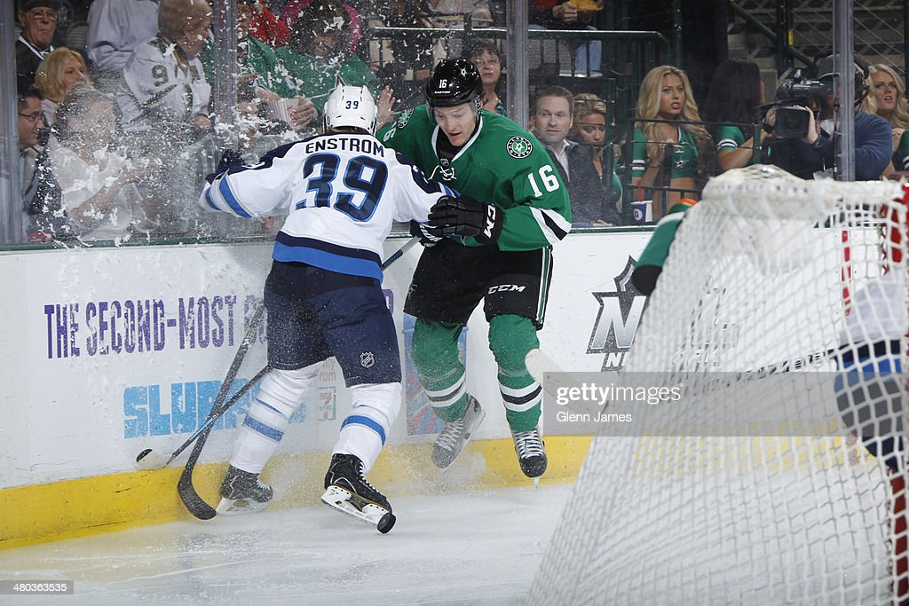 Ryan Garbutt #16 of the Dallas Stars battles along the boards against Tobias Enstrom #39 of the Winnipeg Jets at the American Airlines Center on March 24, 2014 in Dallas, Texas.