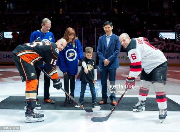 Ryan Getzlaf of the Anaheim Ducks and Andy Greene of the New Jersey Devils pose as Ducks team owners Henry Samueli and Susan Samueli accompany a CHOC...