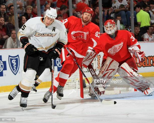 Ryan Getzlaf of the Anaheim Ducks and Johan Franzen of the Detroit Red Wings skate to the puck while Chris Osgood watches during Game Seven of the...