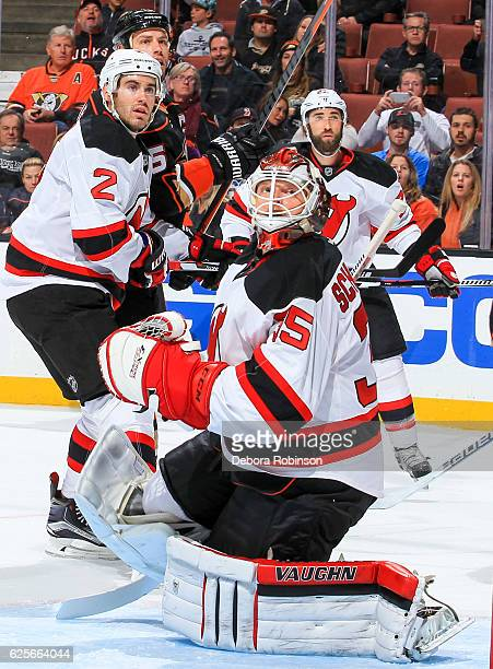 Ryan Getzlaf of the Anaheim Ducks and John Moore goaltender Cory Schneider and Kyle Quincey of the New Jersey Devils watch a high puck during the...