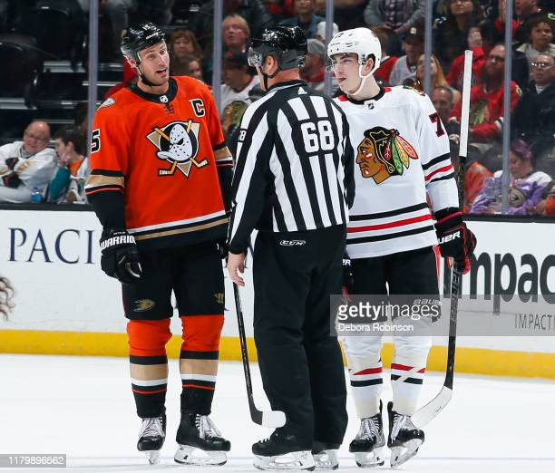 Ryan Getzlaf of the Anaheim Ducks and Kirby Dach of the Chicago Blackhawks talk with linesman Scott Driscoll during the third period of the game at...