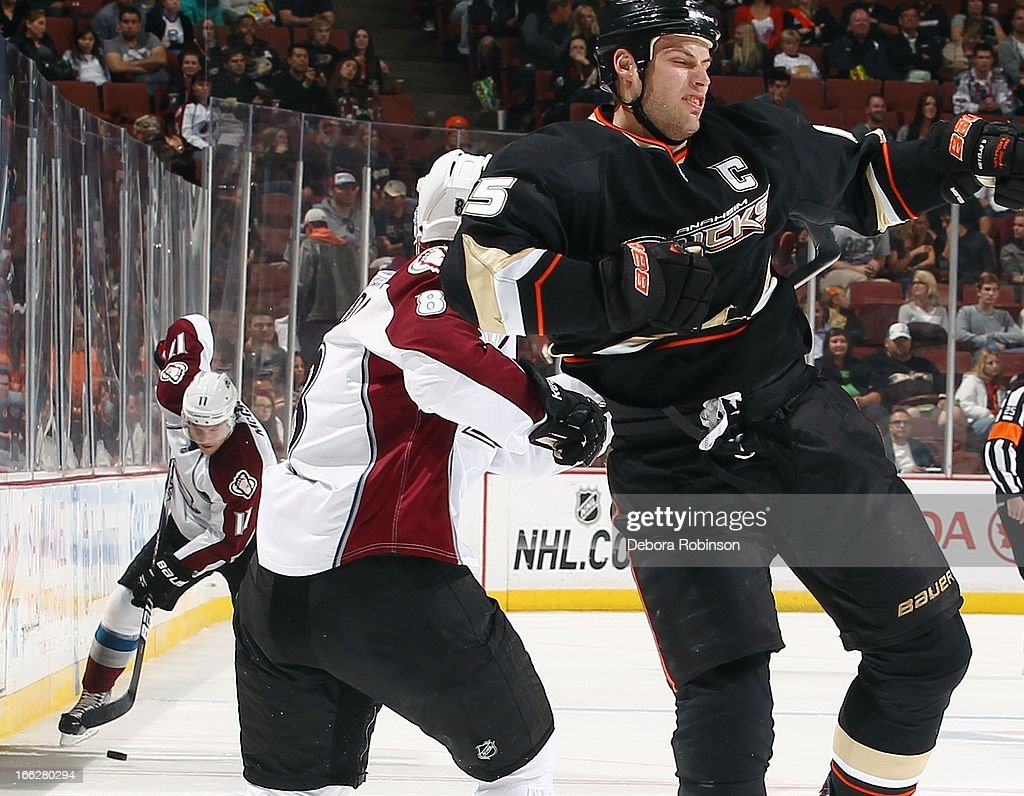 Ryan Getzlaf #15 of the Anaheim Ducks gets jabbed hard in the side by Jan Hejda #8 of the Colorado Avalanche as teammate Jamie McGinn #11 works to move the puck down ice April 10, 2013 at Honda Center in Anaheim, California.