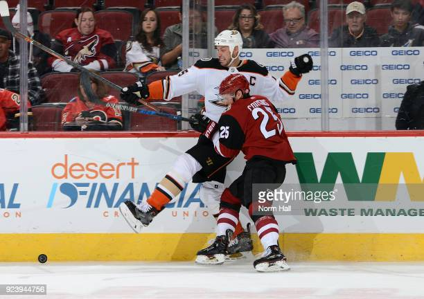 Ryan Getzlaf of the Anaheim Ducks is checked into the boards by Nick Cousins of the Arizona Coyotes during the third period at Gila River Arena on...