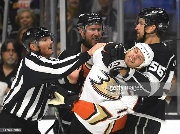 Ryan Getzlaf of the Anaheim Ducks is grabbed by Kurtis MacDermid of the Los Angeles Kings with Jeff Carter, as linesman Darren Gibbs attempts to...