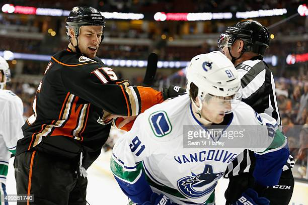 Ryan Getzlaf of the Anaheim Ducks is restrained by linesman Brian Mach as he hits Jared McCann of the Vancouver Canucks during the third period of a...
