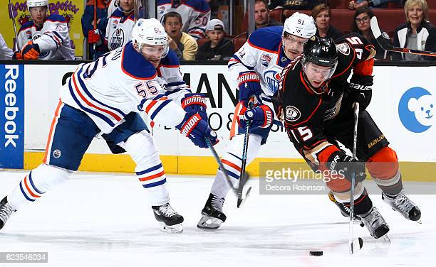 Ryan Getzlaf of the Anaheim Ducks skates with the puck against Mark Letestu and Anton Lander of the Edmonton Oilers on November 15 2016 at Honda...