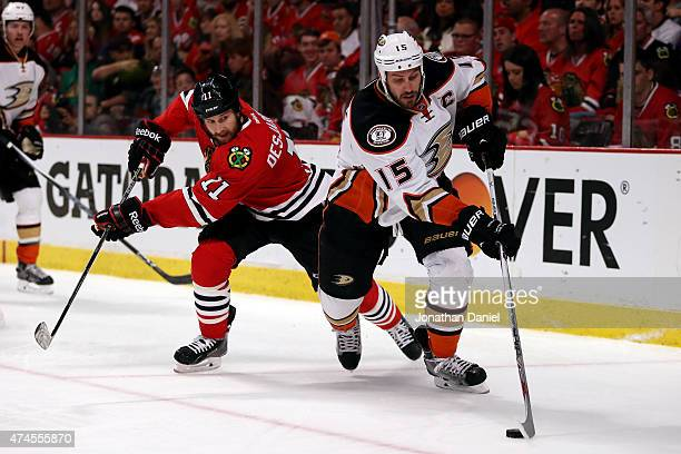 Ryan Getzlaf of the Anaheim Ducks skates with the puck in the second period as Andrew Desjardins of the Chicago Blackhawks defends in Game Four of...