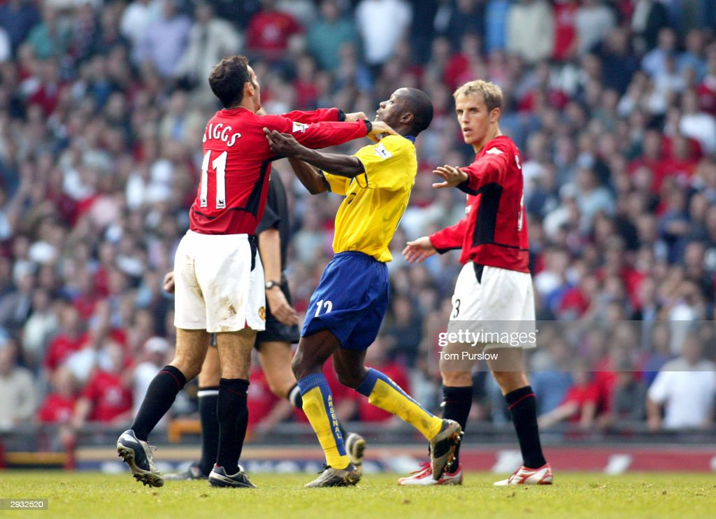 Ryan Giggs and Lauren of Arsenal confront each other during the FA Barclaycard Premiership match between Manchester United v Arsenal at Old Trafford on September 21, 2003 in Manchester, England.