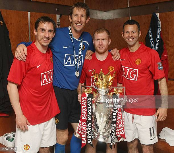 Ryan Giggs Edwin van der Sar Paul Scholes and Gary Neville of Manchester United celebrate with the Premier League trophy in the dressing room after...