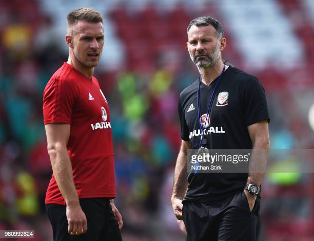Ryan Giggs manager of Wales talks to Aaron Ramsey during a training session a the Racecourse Ground on May 21 2018 in Wrexham Wales