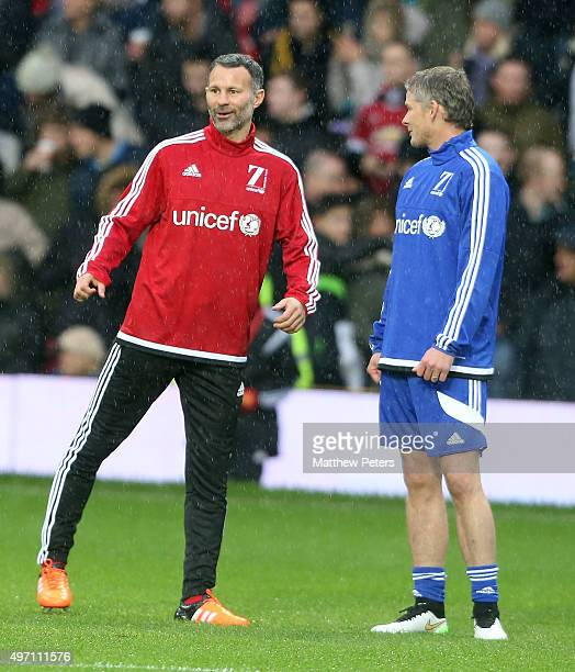 Ryan Giggs of Great Britain and Ireland and Ole Gunnar Solskjaer of the Rest of the World warm up ahead of the David Beckham Match for Children in...