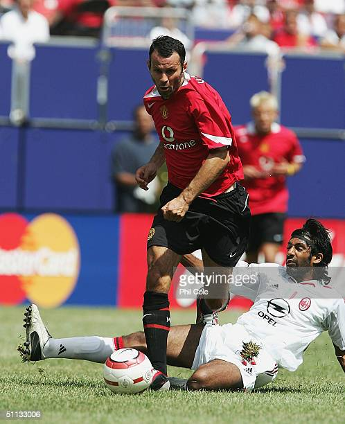 Ryan Giggs of Manchester is tackled by Vikash Dhorasoo of AC Milan during the Champions World Series match between Manchester United and AC Milan at...