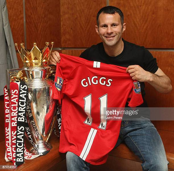 Ryan Giggs of Manchester United celebrates winning his eleventh league title with the Premier League trophy in the dressing room after the Barclays...