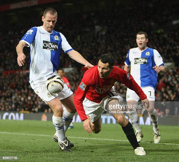 Ryan Giggs of Manchester United clashes with Andre Ooijer of Blackburn Rovers during the Carling Cup QuarterFinal match between Manchester United and...