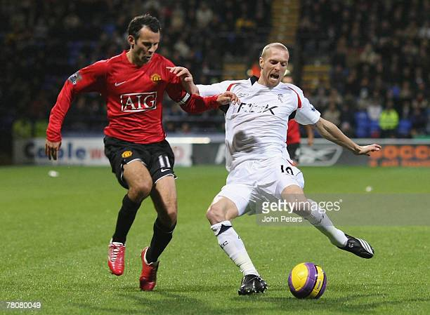 Ryan Giggs of Manchester United clashes with Christian Wilhelmsson of Bolton Wanderers during the Barclays FA Premier League match between Bolton...