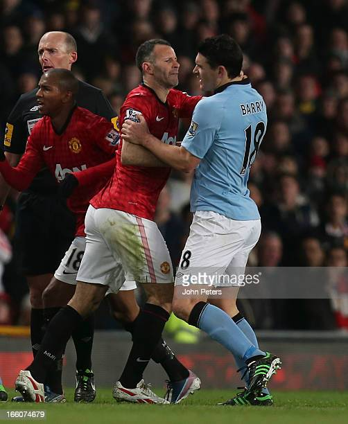 Ryan Giggs of Manchester United clashes with Gareth Barry of Manchester City during the Barclays Premier League match between Manchester United and...