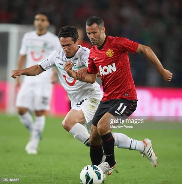 Ryan Giggs of Manchester United clashes with Manuel Schmedebach of 96 Hannover during the pre-season friendly match between Hannover 96 and...