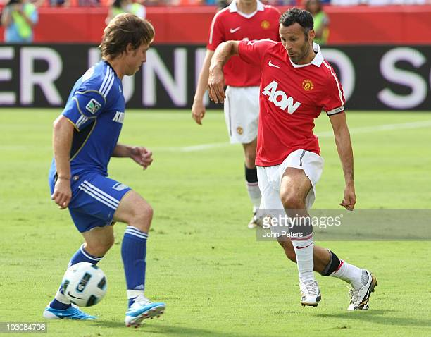 Ryan Giggs of Manchester United clashes with Michael Harrington of Kansas City Wizards during the preseason friendly match between Kansas CIty...