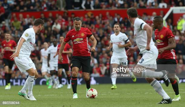 Ryan Giggs of Manchester United in action with Alex Bruce of Michael Carrick AllStars during the Michael Carrick Testimonial match between Manchester...