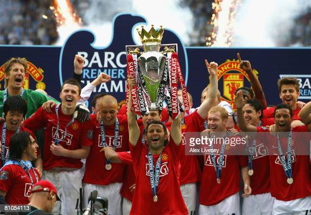 Ryan Giggs of Manchester United lifts the Barclays Premier League trophy as his team mates celebrate following their victory at the end of the...